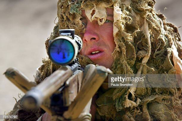 Marine Alasdair Kane a British Royal Marine soldier from the 42nd Commando Lima Brigade goes through training exercises in camouflage using a 338...