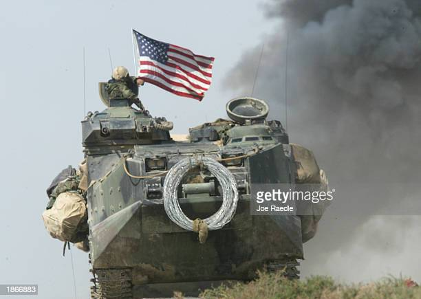 Marine amored assault vehicle from Task Force Tarawa flies the American flag during a gun battle March 23, 2003 in the southern Iraqi city of...