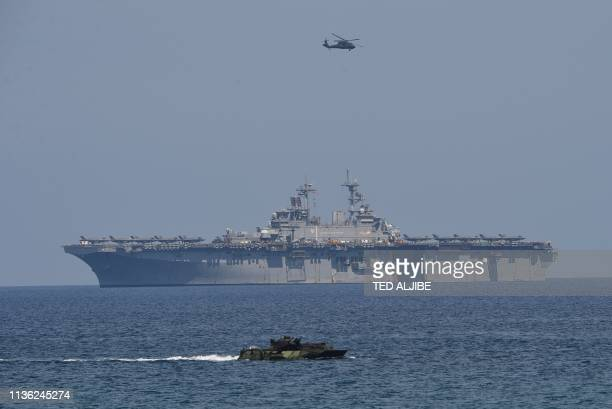 Marine Amphibious Assault Vehicle maneouvers while a seahawk helicopter hovers above the USS Wasp US Navy multipurpose amphibious assault ship during...