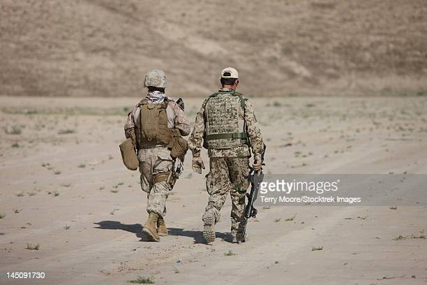 u.s. marine and german coalition soldier walk in a wadi near kunduz, afghanistan. - german military stock pictures, royalty-free photos & images