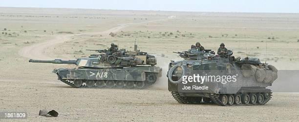 S Marine armored attack vehicle and an M1A1 Abram tank of Task Force Tarawa roll through the Iraqi countryside March 21 2003 on their way to an...
