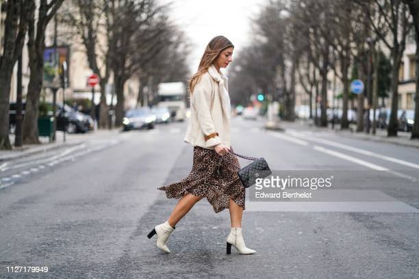 Marine Blanpain wears a white fluffy coat from Loavies a Chanel bag a leopard print skirt a white top a necklace white shoes in the streets of Paris...