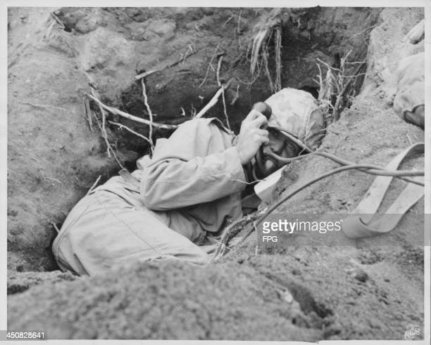 A US marine burrowed into a shallow foxhole during conflict at the edge of Motoyama Airfield at the Battle of Iwo Jima World War Two Japan 1945