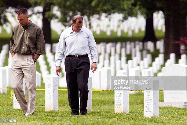 Marine Captain Dan Wittnam and 1st Sgt Jose Henao pay their respects at the grave marker of Marine 1st Lt Frederick Pokorney from 1 / 2 Charlie...