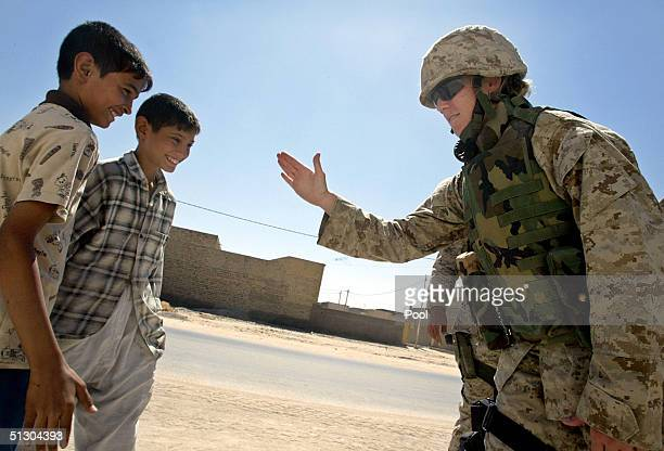 S Marine captain talks with Iraqi boys during a patrol on September 14 2004 in the Iraqi Holy city of Najaf Weeks of battles between the US military...