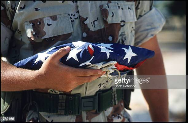 Marine carries a folded American flag March 24 1994 in Mogadishu Somalia The last of the US military presence leaves on a quieter note after much of...