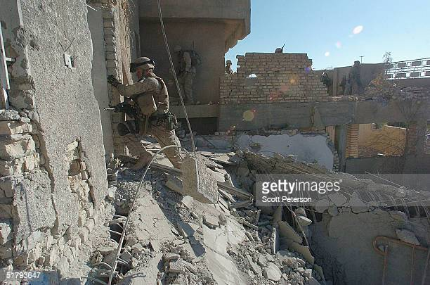 Marine climbs the side of a wrecked building as US Marines of the 1st Light Armored Reconnaissance company as part of 1st Battalion 3rd Marines clear...