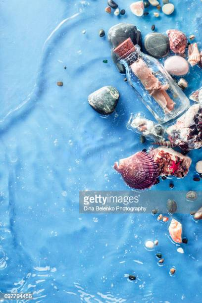 Marine copy space frame with message in a bottle, seashells, pebbles, sand and a ripple of seawave