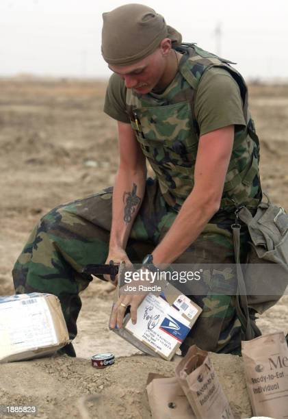 Marine Corporal Jeremy Rains from Terre Haute, Indiana of Task Force Tarawa opens mail from his wife and mother March 30, 2003 in the southern Iraqi...