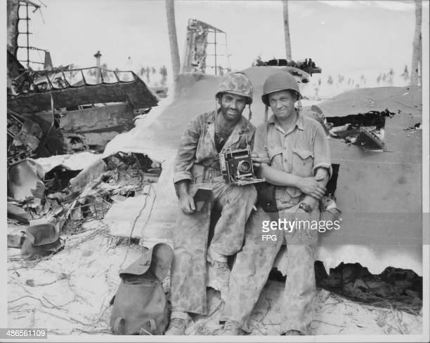 US Marine Corporal Obie R Newcomb and Corporal Raymond Matjasic posing beside the wreckage of a Japanese plane during the Pacific Campaign of World...