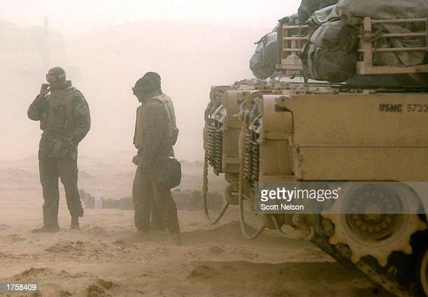 S Marine Corps 1st Tank Battallion tank crews wait out a blinding sand storm during exercises February 3 2003 near the Iraqi border in Kuwait Both...