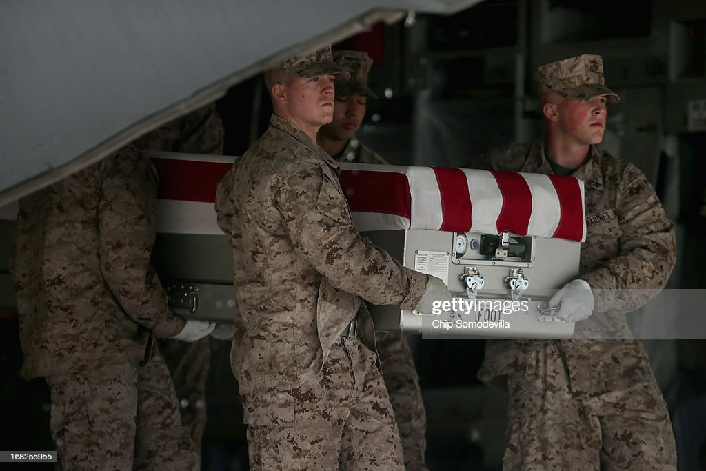 S. Marine Corps carry team carries the flag-draped transfer case with the remains of Marine Cpl. David M. Sonka, 23, of Parker, Colorado off of a C-17 on the tarmac at Dover Air Force Base May 7, 2013 in Dover, Delaware. Assigned to 2nd Marine Special Operations Battalion out of Camp Lejeune, North Carolina, Sonka and one other Marine died May 4, while conducting combat operations in Farah province, Afghanistan.
