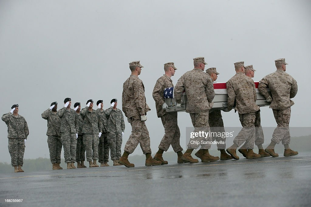 S. Marine Corps carry team carries the flag-draped transfer case with the remains of Marine Cpl. David M. Sonka, 23, of Parker, Colorado across the tarmac in the pouring rain at Dover Air Force Base May 7, 2013 in Dover, Delaware. Assigned to 2nd Marine Special Operations Battalion out of Camp Lejeune, North Carolina, Sonka and one other Marine died May 4, while conducting combat operations in Farah province, Afghanistan.