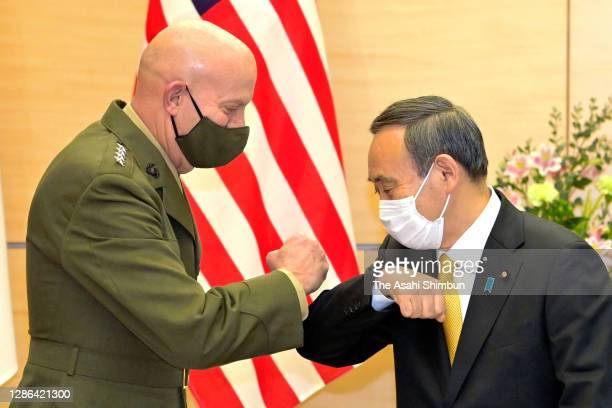Marine Corps Commander General David Berger and Japanese Prime Minister Yoshihide Suga elbow bump prior to their meeting at the prime minister's...