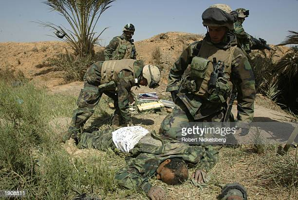 Marine corpsman of the 1st Marine Division treats a wounded Iraqi Army officer April 1, 2003 in Diwaniya, Iraq. The officer later died from blood...