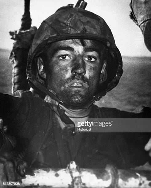 A Marine covered in sweat grime and coral dust boards a Coast Guard assault transport in February 1944 after two days and nights of fighting on...