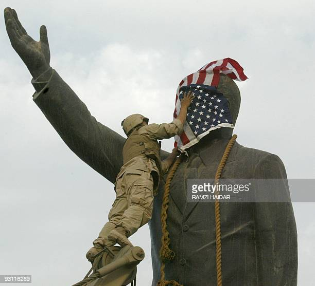 Marine covers the face of Iraqi President Saddam Hussein's statue with the US flag in Baghdad's alFardous square 09 April 2003 The flag was removed...