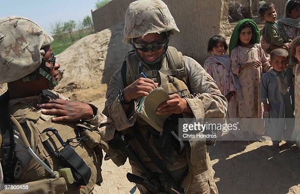 US Marine Cpl Ernstar Coriolan of Brooklyn New York and Cpl Ramona Brown of Fayetteville North Carolina look over notes while young Pashtun girls...