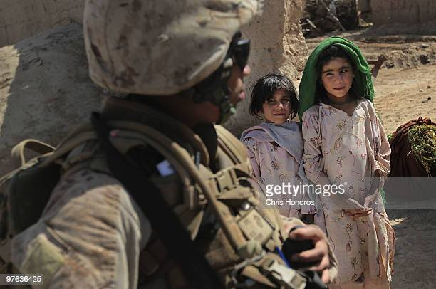 Marine Cpl Ramona Brown of Fayetteville North Carolina stands while young Pashtun girls watch March 11 2010 in a hamlet near Khan Neshin in Helmand...