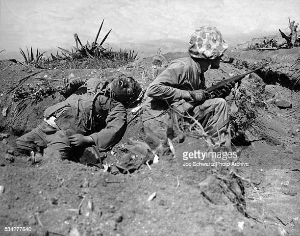Marine Crouches Near Corpse of Japanese Officer