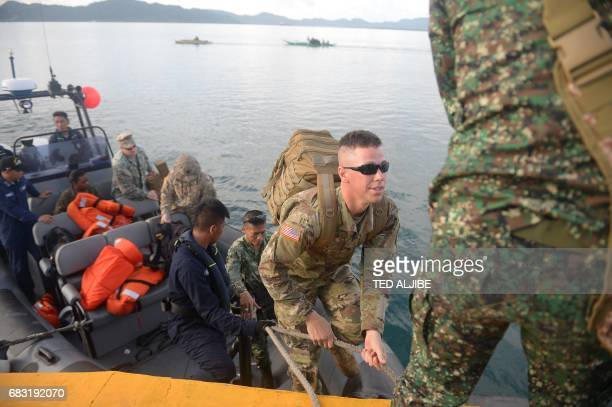 A US marine disembarks from a speed boat during a simulation of a disaster drill as part of the annual joint PhilippinesUS military exercise at the...