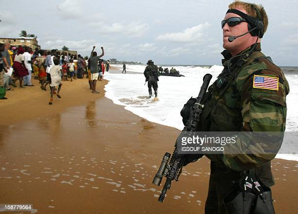 Marine disembarks on a Monrovia beach as others are cheered by Monrovians 18 August 2003 to inspect the beach as they declared to journalists on the...