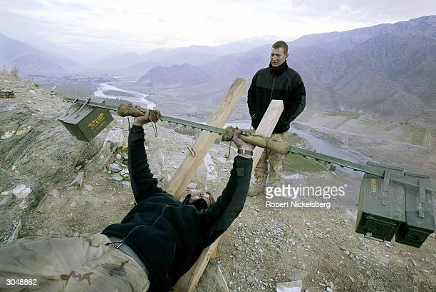 Marine does 135-pound bench presses above a U.S. Military observation post in Asadabad, Afghanistan, 10 kms from the Pakistani border, January 31,...