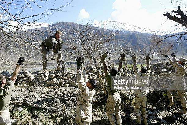 US Marine Engineers based in Asadabad the capital of Kunar Province stretch additional razor wire along the perimeter of the Coalition Forces base...