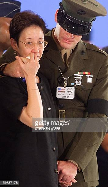 Marine escort consoles an unidentified member of the Alaganga family at a ceremony 13 August at Andrews Air Force Base in Maryland honoring the men...