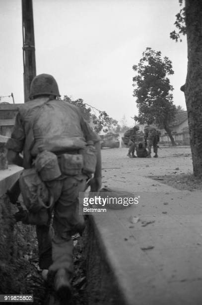A US marine fights from a ditch in Hue South Vietnam as other marines drag a wounded colleague to safety