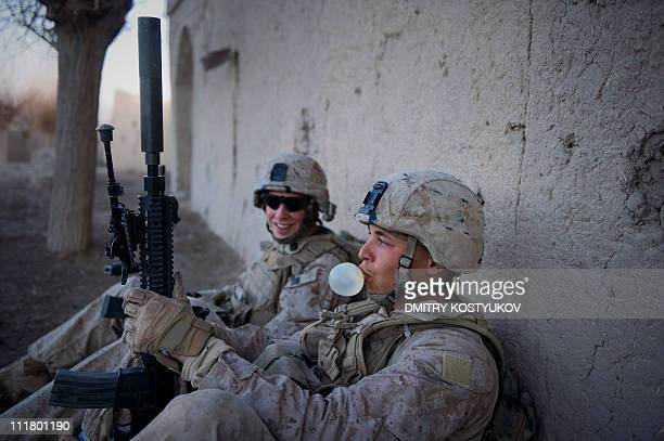 Marine from 1st Battalion 8th Marines blows bubbles from chewing gum as he waits with a colleague to patrol the area around new Mirage base on the...