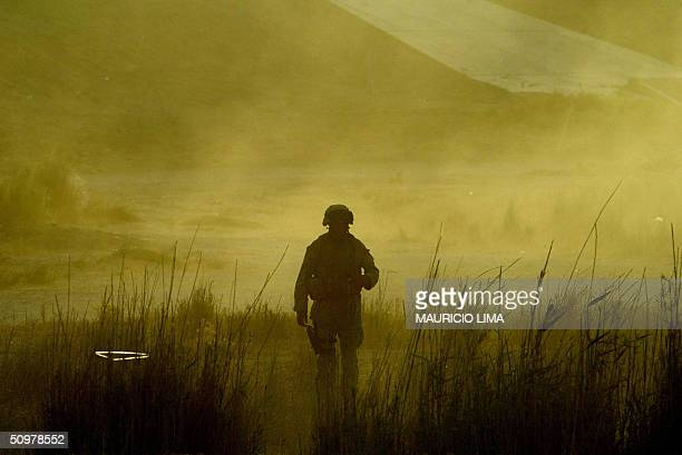US marine from 2nd Battalion 1st Marines Fox Company walks through the dust during a personnel replacement at a temporary base alongside the highway...
