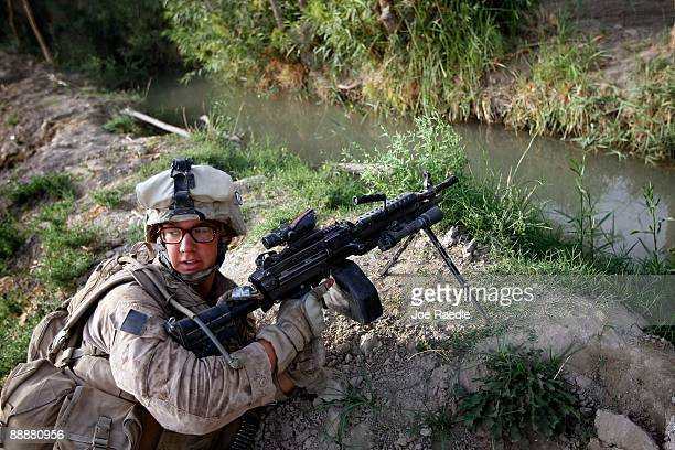 S Marine from 2nd Marine Expeditionary Brigade RCT 2nd Battalion 8th Marines Echo Co takes up a defensive position as he patrols through a village on...