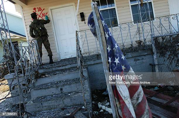 Marine from Camp Lejeune NC marks a home to indicate he found no occupants as houses in the lower Ninth Ward are checked for bodies or people who are...