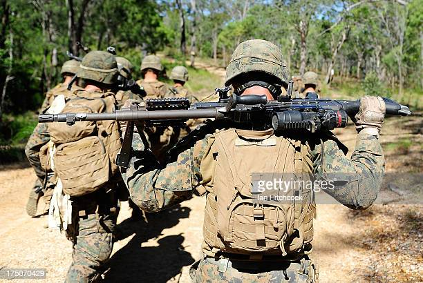 Marine from Golf Company Battalion Landing Team 2/4 carries his M240G Medium Machine Gun across his shoulders whilst participating in a live fire...