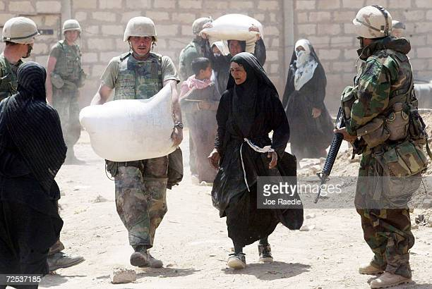 Marine from Task Force Tarawa helps woman with bag of flour from after opening a warehouse April 1, 2003 in the southern Iraqi city of Nasiriyah. The...