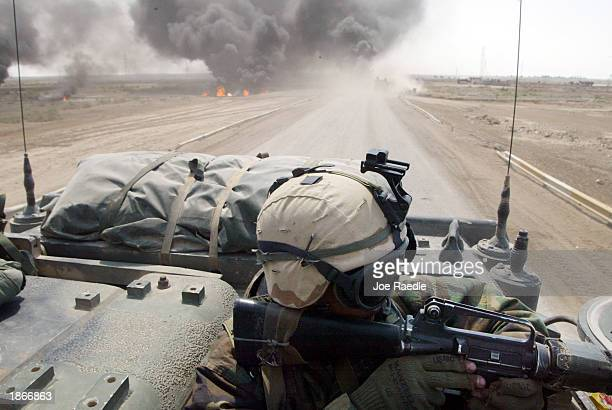 S Marine from Task Force Tarawa rides in an armored assault vehicle passing a burning vehicle while engaging Iraqi forces March 23 2003 in the...
