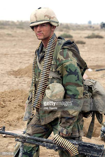 Marine from Task Force Tarawa walks with his ammunition and weapon March 24, 2003 in the southern Iraqi city of Nasiriyah. The Marines have had...