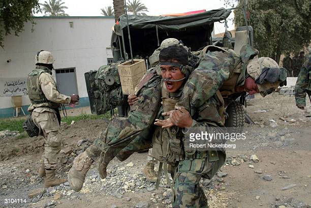 A US Marine from the 1st Marine Division carries a wounded comrade after one of their amphibious assault vehicles received a direct Iraqi artillery...