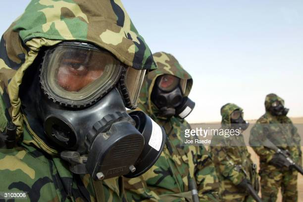 S Marine from the 1st Marine Division Cpl Quintin Bishop of Cincinnati Ohio and others wear their chemical masks as they practice for a chemical...