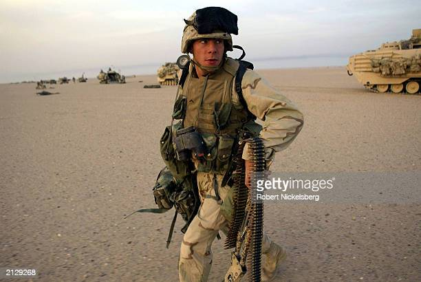 Marine from the 1st Marine Division moves off to set a security perimeter approximately 20 kms south of the Iraqi border in the final deployment area...