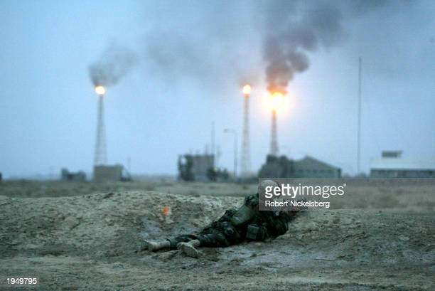 A Marine from the 1st Marine Division takes fire from Iraqi Army stragglers near Basra's main oil refinery March 21 2003 25 km south of Basra Iraq A...