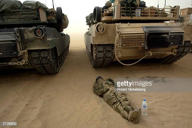 Marine from the 1st Marine Division Tanks rests behind a M1A1 Abrams tank during a 45 mph sandstorm February 3 while waiting for sighting in...