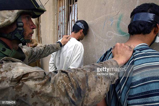 US marine from the 3/5 Lima company hold against the wall two suspected insurgents in the Jolan district of the restive city of Fallujah 12 November...
