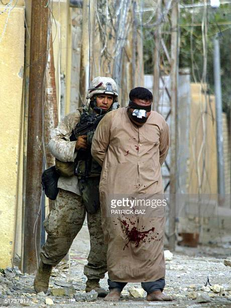 US marine from the 3/5 Lima company leads away a gagged and bound man during operations in the restive city of Fallujah 13 November 2004 west of...