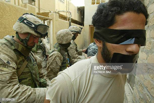 US marine from the 3/5 Lima company leads away a suspected insurgent in the Jolan district of the restive city of Fallujah 12 November 2004 50 kms...