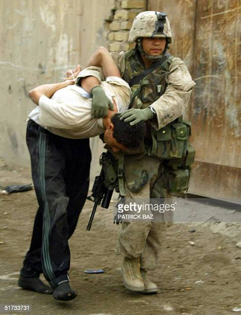 US marine from the 3/5 Lima company takes away a suspected insurgent in the Jolan district of the restive city of Fallujah 12 November 2004 50 kms...
