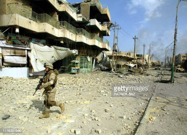 Marine from the 3/5 Lima company walks towards a destroyed building along the main street in the restive city of Fallujah,14 November 2004, 50 kms...