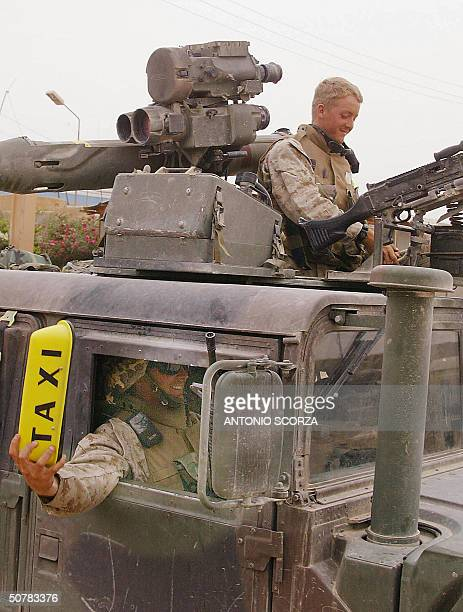 US marine from the First Battalion 5th Marines Bravo Company puts a 'Taxi' sign atop of their Humvee as US troops prepared to draw back from the...