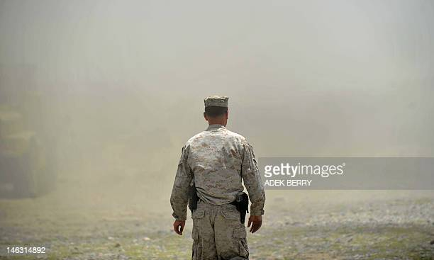 US Marine Gunnery Sergeant Traves Bouten with Explosive Ordnance Disposal from 1st Battalion 7th Marines Regiment walks after a controlled explosion...